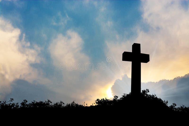 Σκιαγραφήστε το σταυρό πέρα από το θολωμένο υπόβαθρο ηλιοβασιλέματος στοκ φωτογραφία