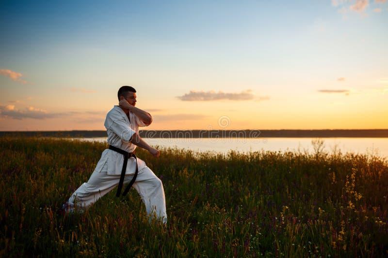 Σκιαγραφία αθλητικό karate κατάρτισης ατόμων στον τομέα στην ανατολή στοκ φωτογραφία με δικαίωμα ελεύθερης χρήσης