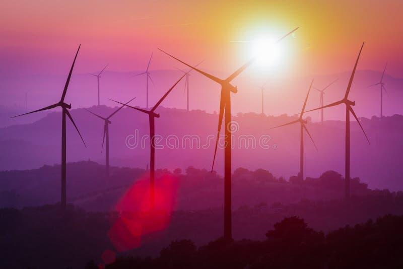Σκιαγραφία ανεμοστροβίλων στα βουνά στο ηλιοβασίλεμα στοκ εικόνα