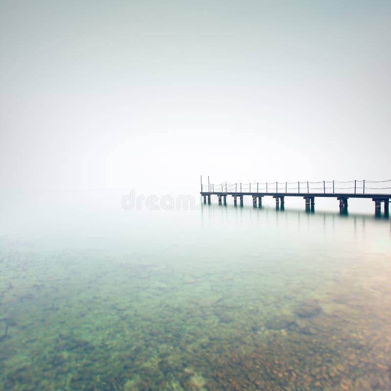 Η αποβάθρα ή ο λιμενοβραχίονας σκιαγραφεί σε μια ομιχλώδη λίμνη. Λίμνη Garda, Ιταλία στοκ εικόνες