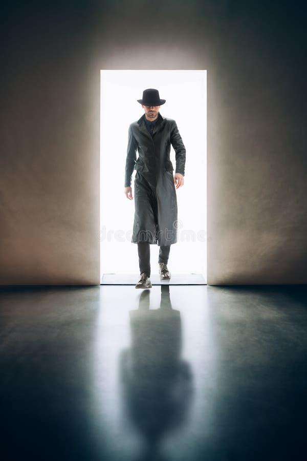 Σκιαγραφία ατόμων που προέρχεται από το φως του ανοίγματος της πόρτας στο σκοτεινό roo στοκ εικόνες