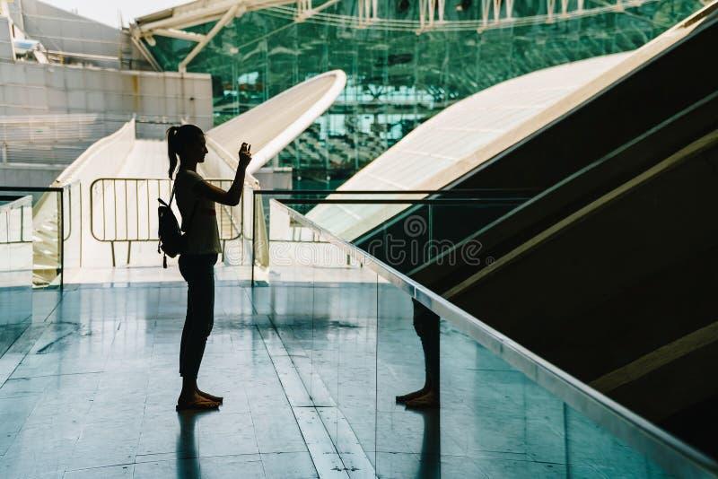 Σκιαγραφία ενάντια στο φως της νέας γυναίκας που παίρνει τις φωτογραφίες στοκ φωτογραφία με δικαίωμα ελεύθερης χρήσης