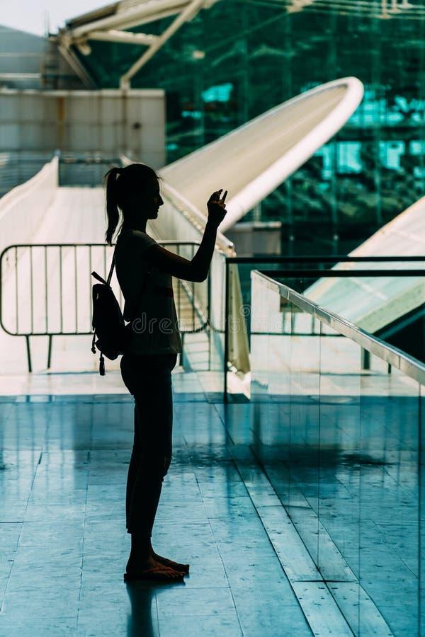 Σκιαγραφία ενάντια στο φως της νέας γυναίκας που παίρνει τις φωτογραφίες στοκ φωτογραφίες
