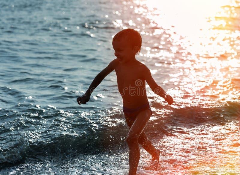 Σκιαγραφία ενός αγοριού που τρέχει κατά μήκος της παραλίας στοκ εικόνες με δικαίωμα ελεύθερης χρήσης