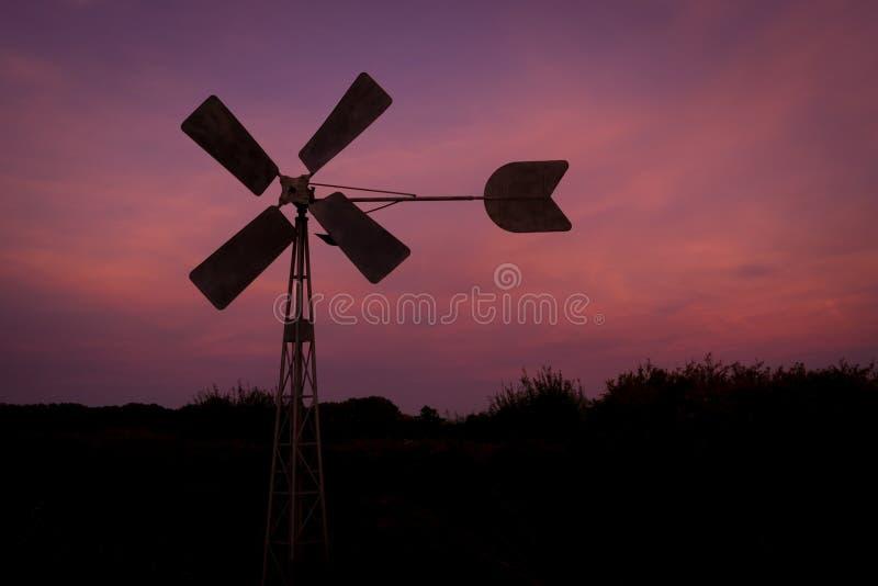 Σκιαγραφία ενός ανεμόμυλου ενάντια σε έναν πορφυρό ουρανό βραδιού κοντά στο γκούντα, Ολλανδία στοκ φωτογραφία