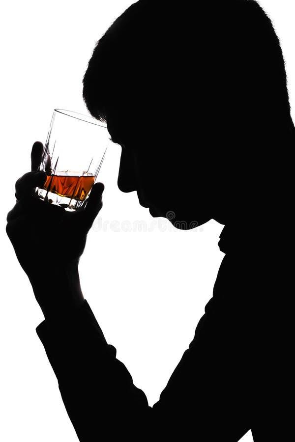 Σκιαγραφία ενός ατόμου με ένα ποτήρι του κονιάκ στο μέτωπό του στοκ φωτογραφίες