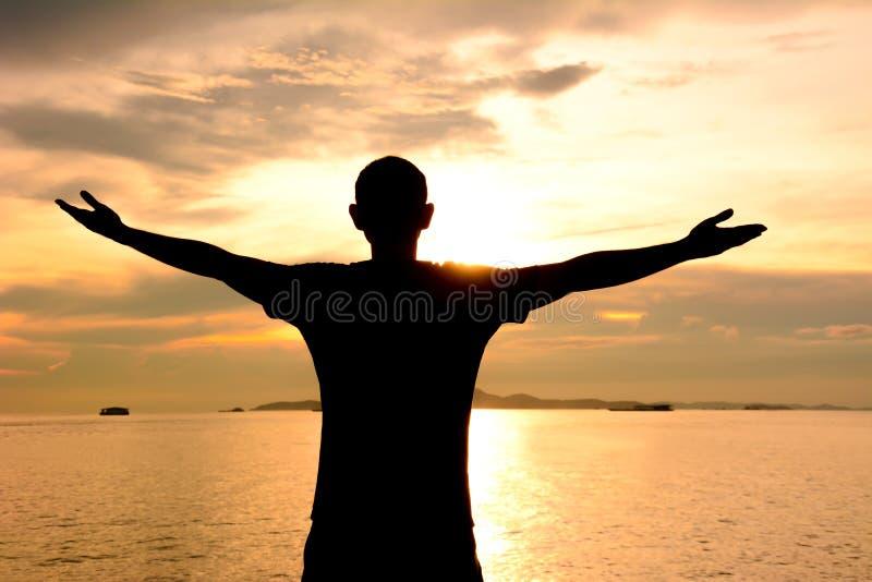 Σκιαγραφία ενός ατόμου που αυξάνει τα όπλα του στο ηλιοβασίλεμα στο υπόβαθρο θάλασσας στοκ εικόνες με δικαίωμα ελεύθερης χρήσης