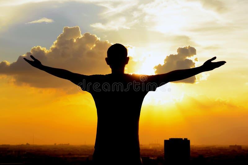 Σκιαγραφία ενός ατόμου που αυξάνει τα όπλα του στο υπόβαθρο ουρανού λυκόφατος στοκ εικόνες