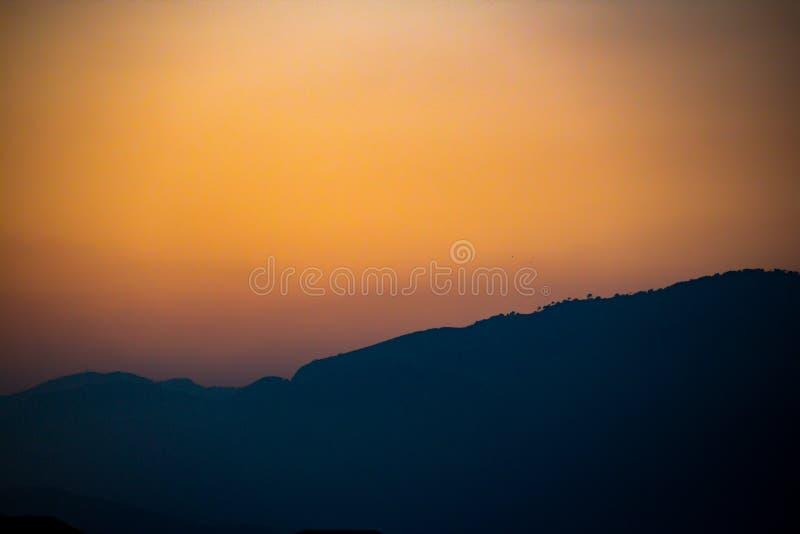 Σκιαγραφία ενός βουνού στο βαθύ πορτοκαλή ουρανό στοκ εικόνες