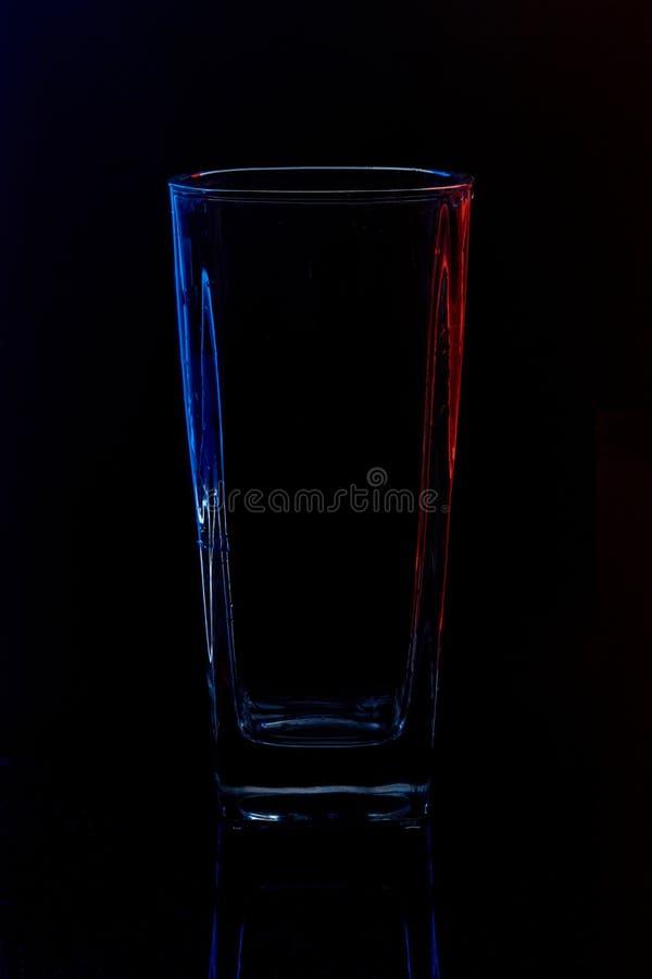 Σκιαγραφία ενός γυαλιού με το νερό σε ένα μαύρο υπόβαθρο στοκ φωτογραφία με δικαίωμα ελεύθερης χρήσης