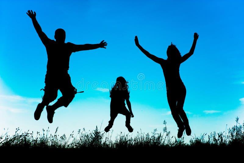 Σκιαγραφία ενός ευτυχούς ενεργού οικογενειακού άλματος στοκ εικόνες