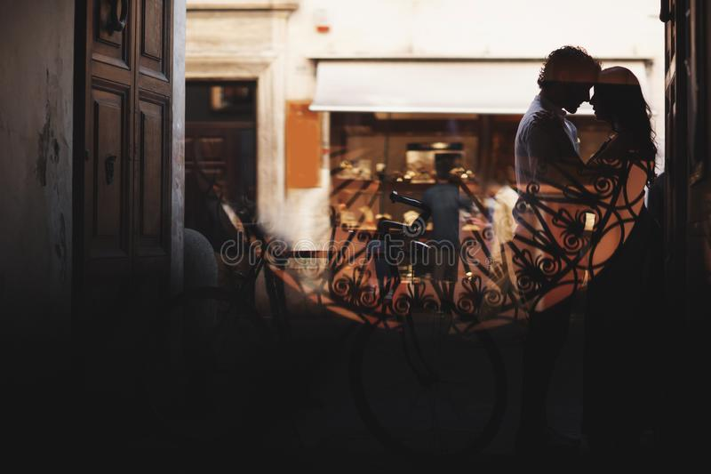 Σκιαγραφία ενός ζεύγους αγάπης Ο άνδρας και η γυναίκα αγκαλιάζουν ήπια Περίπατος με ένα ποδήλατο στοκ εικόνες