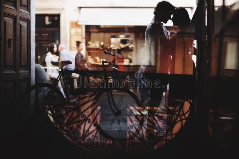 Σκιαγραφία ενός ζεύγους αγάπης Ο άνδρας και η γυναίκα αγκαλιάζουν ήπια Περίπατος με ένα ποδήλατο στοκ εικόνα