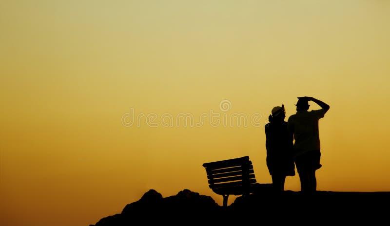 Σκιαγραφία ενός ζεύγους ερωτευμένου στην παραλία στο ηλιοβασίλεμα ιστορία αγάπης φιλήματος κοριτσιών κήπων αγοριών Άνδρας και μια στοκ εικόνες