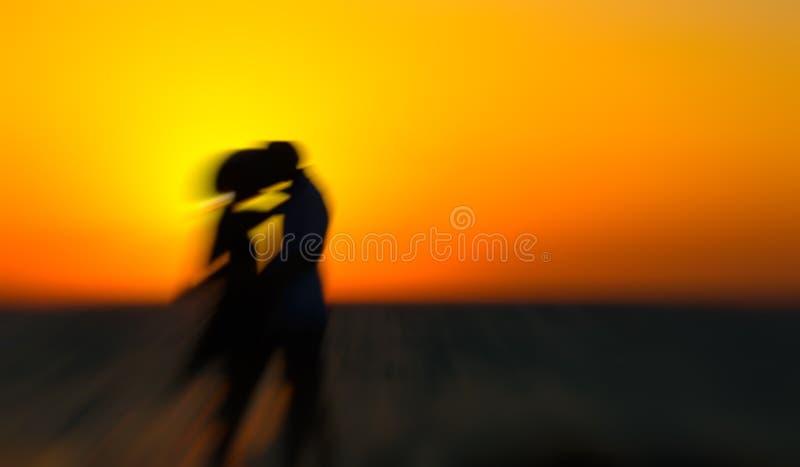 Σκιαγραφία ενός ζεύγους ερωτευμένου στην παραλία στο ηλιοβασίλεμα Αφηρημένη επίδραση θαμπάδων κινήσεων στοκ φωτογραφία