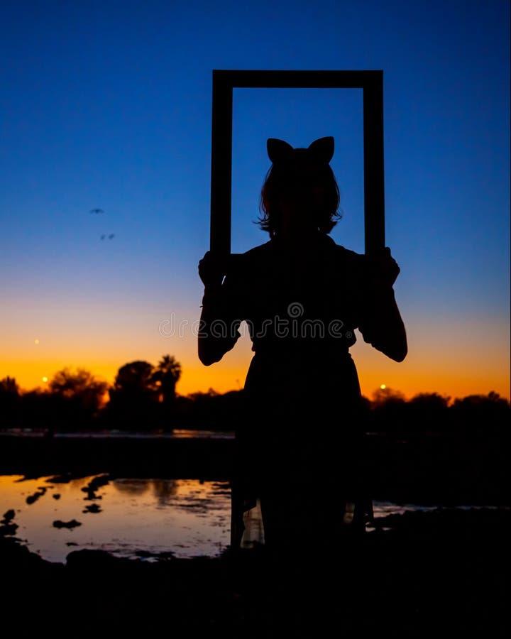 Σκιαγραφία ενός κοριτσιού με τα αυτιά γατών που κοιτάζει μέσω μιας εικόνας FR στοκ εικόνα
