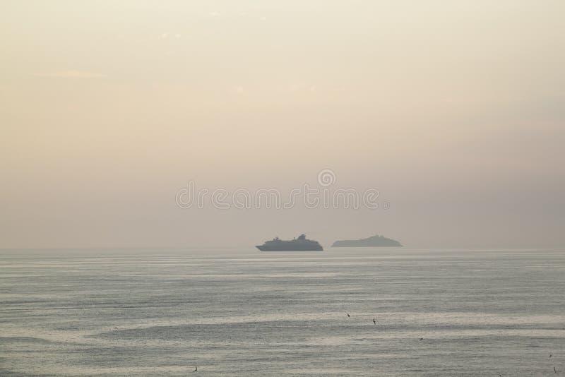 σκιαγραφία ενός κρουαζιερόπλοιου στο λυκόφως ηλιοβασιλέματος στα νερά στοκ εικόνα