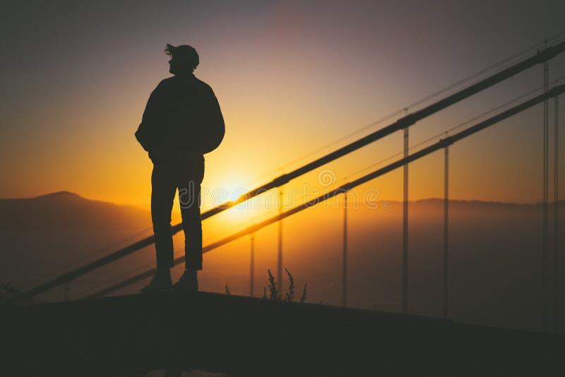 Σκιαγραφία ενός νέου αρσενικού που στέκεται στη σκάλα πίσω από τις ράγες σκαλοπατιών με την όμορφη άποψη ηλιοβασιλέματος στοκ φωτογραφία
