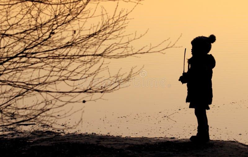 Σκιαγραφία ενός παιδιού που παίζει στη φύση στο ηλιοβασίλεμα στοκ φωτογραφίες με δικαίωμα ελεύθερης χρήσης
