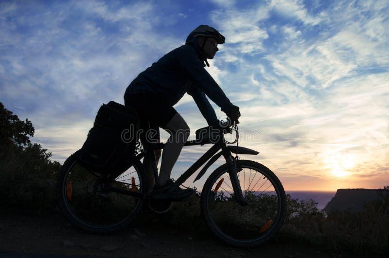 Σκιαγραφία ενός ποδηλάτη στο υπόβαθρο του νεφελώδους ουρανού στοκ εικόνα