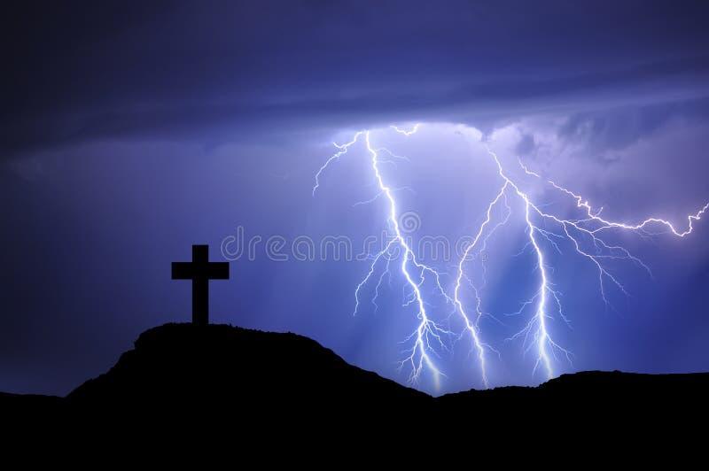Σκιαγραφία ενός σταυρού στο βουνό με τις ακτίνες και το άσχημο καιρό στοκ φωτογραφία με δικαίωμα ελεύθερης χρήσης