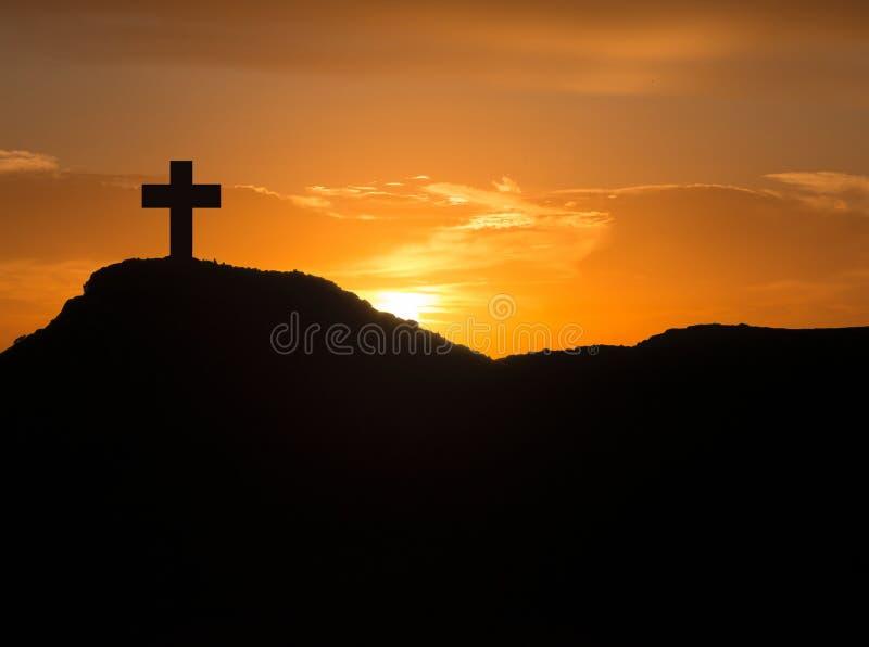 Σκιαγραφία ενός σταυρού στο βουνό στην ανατολή στοκ φωτογραφίες