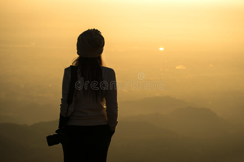 Σκιαγραφία ενός φωτογράφου γυναικών που στέκεται στον ξηρό τομέα χλόης στοκ φωτογραφία