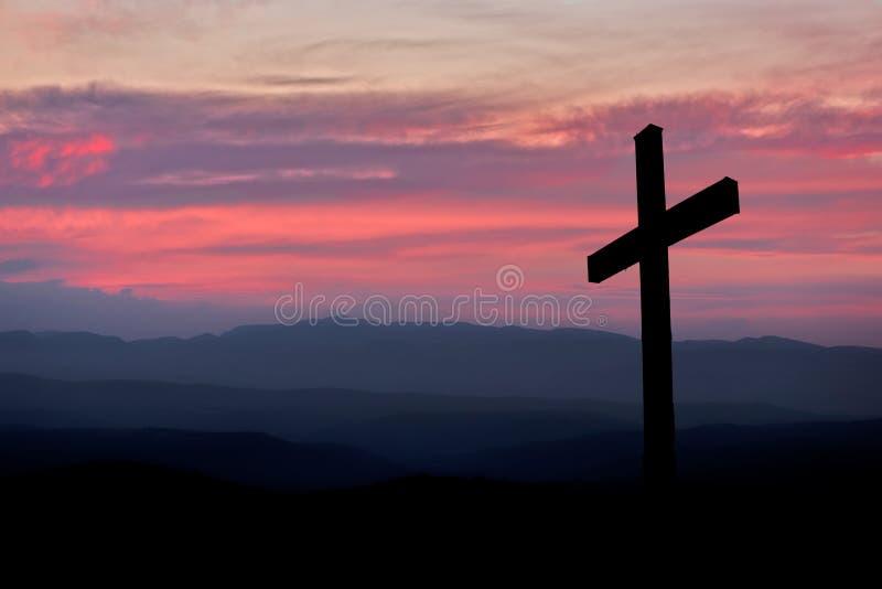 Σκιαγραφία ενός χριστιανικού σταυρού με ένα ηλιοβασίλεμα στα βουνά στοκ φωτογραφίες