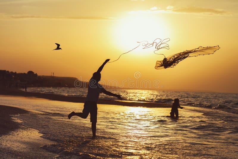 Σκιαγραφία ενός ψαρά στο ηλιοβασίλεμα που ρίχνει ένα δίχτυ του ψαρέματος στοκ εικόνες