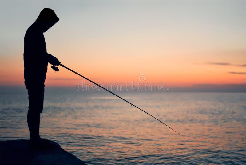 Σκιαγραφία ενός ψαρά στο ηλιοβασίλεμα στοκ φωτογραφία με δικαίωμα ελεύθερης χρήσης