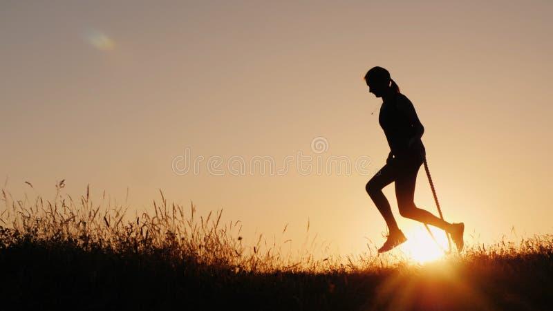 Σκιαγραφία μιας γυναίκας - που πηδά μέσω του σχοινιού στο ηλιοβασίλεμα στοκ εικόνες