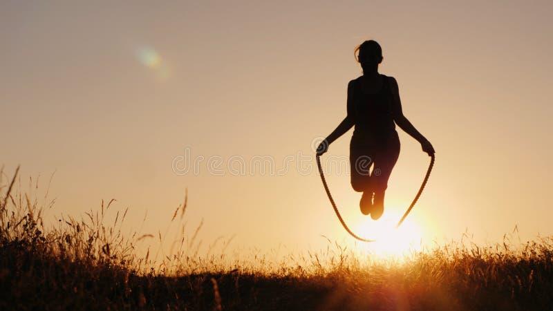 Σκιαγραφία μιας γυναίκας - που πηδά μέσω του σχοινιού στο ηλιοβασίλεμα στοκ φωτογραφίες