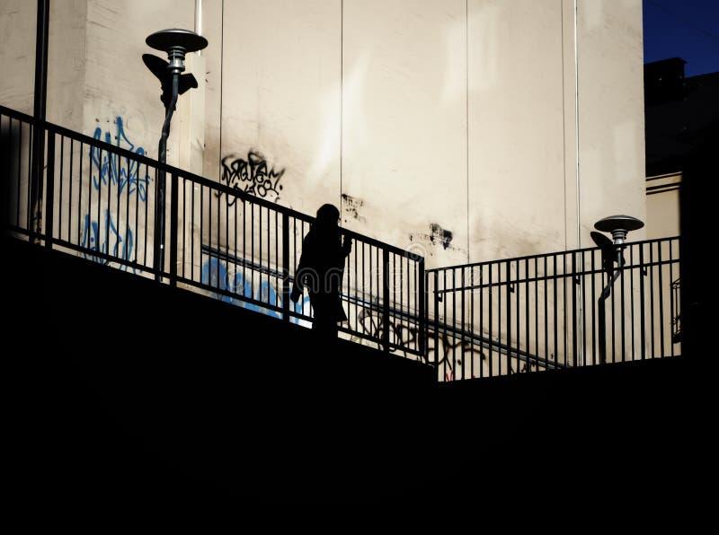 Σκιαγραφία μιας γυναίκας στην ανυψωμένη διάβαση πεζών στοκ εικόνες