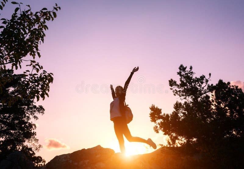 Σκιαγραφία μιας ευτυχούς νέας γυναίκας στα βουνά στο ηλιοβασίλεμα στοκ εικόνες