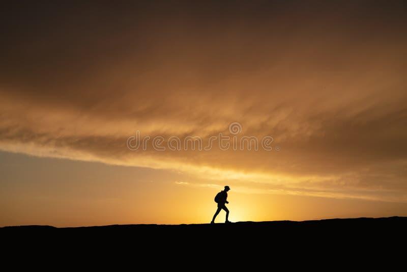 Σκιαγραφία μιας μόνης γυναίκας που περπατά στο ηλιοβασίλεμα σε έναν λόφο στοκ φωτογραφία