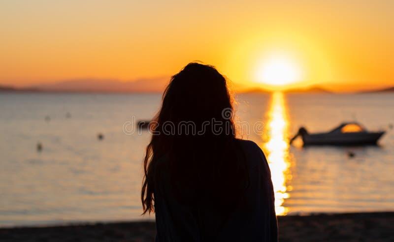 Σκιαγραφία μιας νέας γυναίκας μπροστά από ένα ηλιοβασίλεμα στην παραλία, με τις βάρκες και τα βουνά Οι διακοπές χαλαρώνουν τη σκη στοκ εικόνες