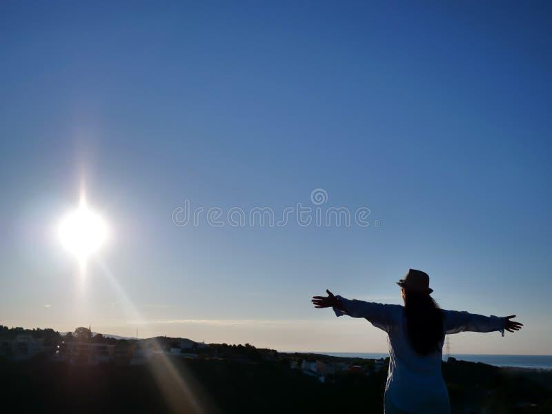 Σκιαγραφία μιας νέας γυναίκας brunette με τα αυξημένα όπλα στο υπόβαθρο της ανατολής, οι ακτίνες του ήλιου, copyspace στοκ εικόνες