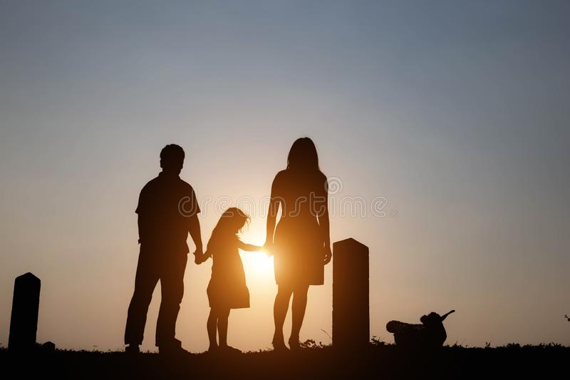 Σκιαγραφία μιας οικογένειας περιλαμβάνοντας έναν πατέρα, μια μητέρα και μια ευτυχή οικογένεια δύο παιδιών το ηλιοβασίλεμα Έννοια  στοκ εικόνες με δικαίωμα ελεύθερης χρήσης