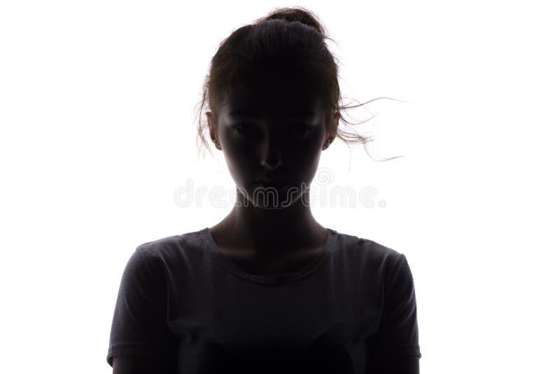Σκιαγραφία μιας σοβαρής και βέβαιας νέας γυναίκας που κοιτάζει straigh σε ένα απομονωμένο λευκό υπόβαθρο στοκ φωτογραφία