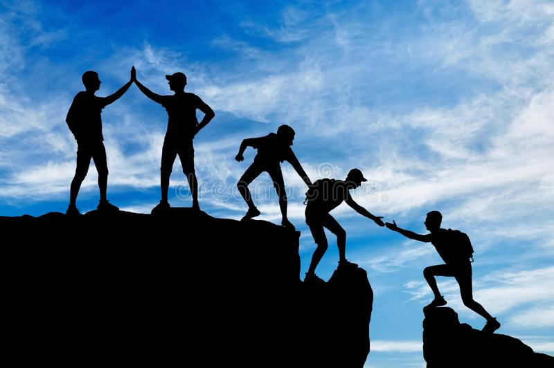 Σκιαγραφία πέντε ορειβατών που υπερνικούν το μόχθο της εργασίας σε μια ομάδα στοκ φωτογραφία