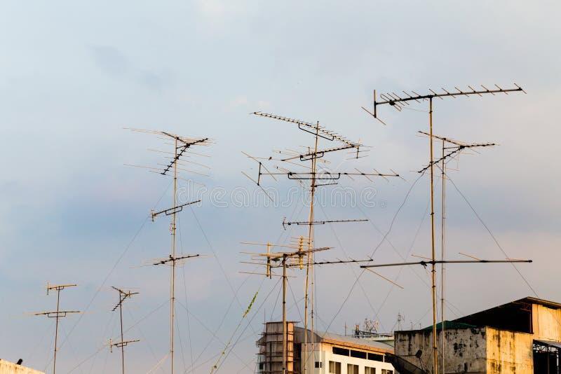Σκιαγραφία, πύργοι τηλεπικοινωνιών με τις κεραίες TV και δορυφορικό πιάτο στο ηλιοβασίλεμα Κεραίες και δορυφόρος πολλές εγχώριας  στοκ φωτογραφία