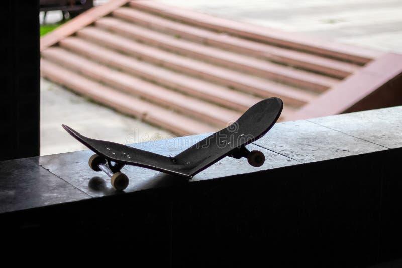 Σκιαγραφία σπασμένο skateboard δίπλα στα σκαλοπάτια στοκ εικόνα