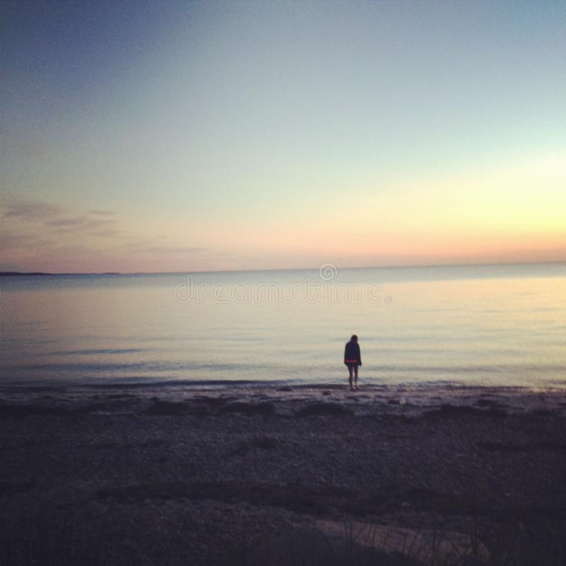 Σκιαγραφία στην παραλία στο ηλιοβασίλεμα στοκ εικόνες με δικαίωμα ελεύθερης χρήσης