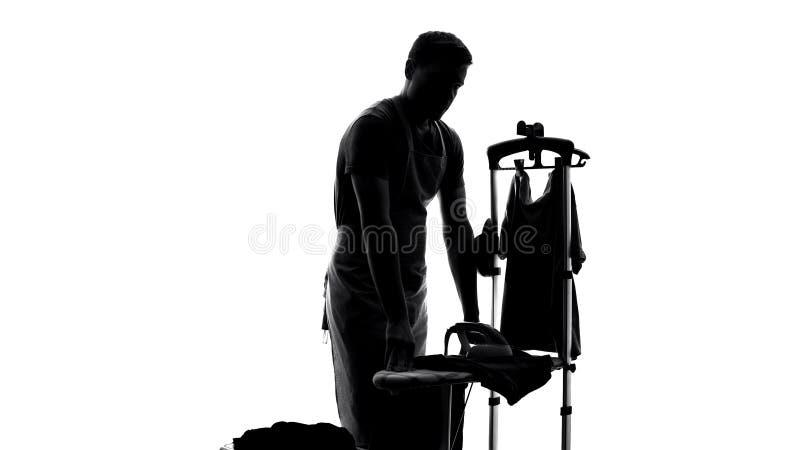 Σκιαγραφία συζύγων στο συναίσθημα ποδιών που κουράζεται του σιδερώματος των ενδυμάτων, ρουτίνα οικιακών στοκ φωτογραφία με δικαίωμα ελεύθερης χρήσης
