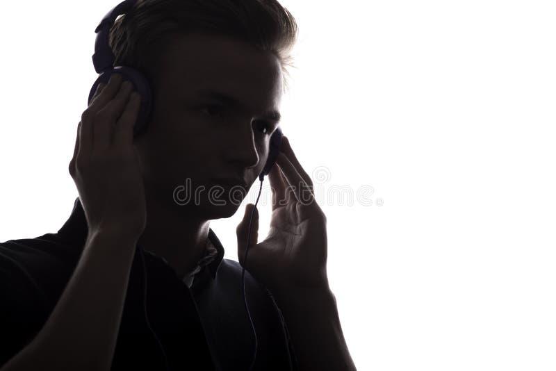 Σκιαγραφία σχεδιαγράμματος προσώπου του ακούσματος εφήβων φίλων της μουσικής το αγαπημένο τραγούδι στα ακουστικά, όμορφος νεαρός  στοκ φωτογραφίες με δικαίωμα ελεύθερης χρήσης