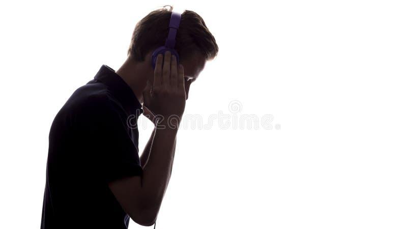 Σκιαγραφία σχεδιαγράμματος προσώπου του ακούσματος εφήβων φίλων της μουσικής το αγαπημένο τραγούδι στα ακουστικά, όμορφος νεαρός  στοκ εικόνες με δικαίωμα ελεύθερης χρήσης