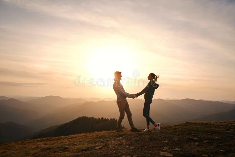 Σκιαγραφία της αγάπης του ζεύγους που στέκεται στην άκρη του βουνού και που κρατά τα χέρια στον ουρανό ηλιοβασιλέματος και το υπό στοκ εικόνες
