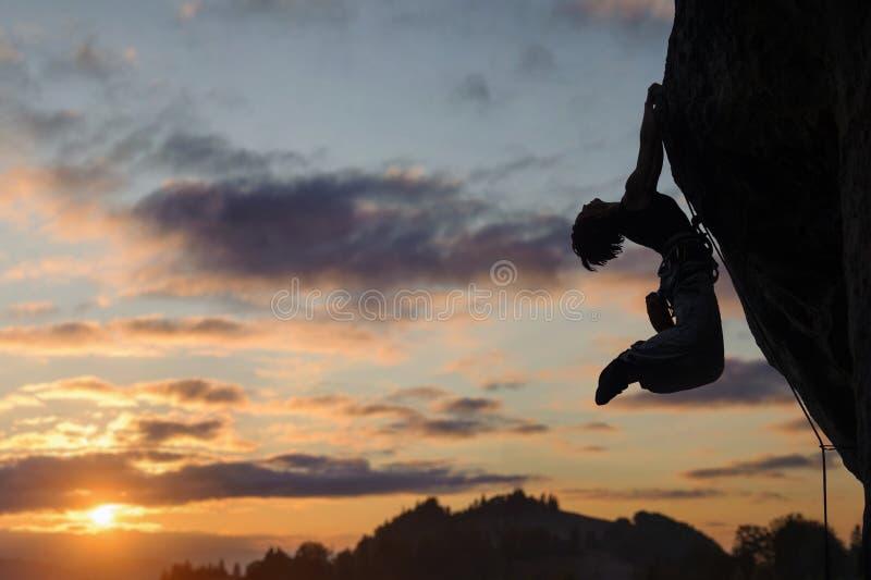 Σκιαγραφία της αθλητικής γυναίκας που αναρριχείται στον απότομο τοίχο βράχου στοκ εικόνα με δικαίωμα ελεύθερης χρήσης