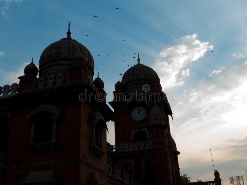 Σκιαγραφία της αρχαίας δομής, πουλιά στον ουρανό και sunrays στοκ φωτογραφία
