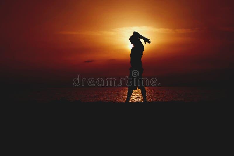 Σκιαγραφία της γιόγκας άσκησης νεαρών άνδρων Πορτοκαλί ηλιοβασίλεμα Seacoast στοκ φωτογραφία